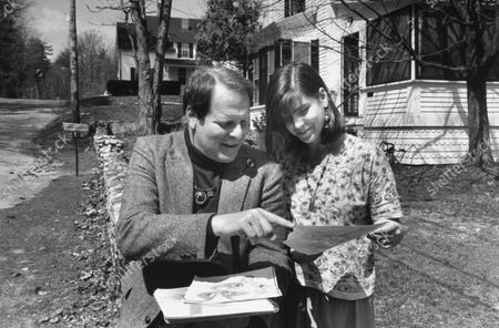 Author Richard Howard looking at notebook w. 16-year-old daughter Katherine, outside home.