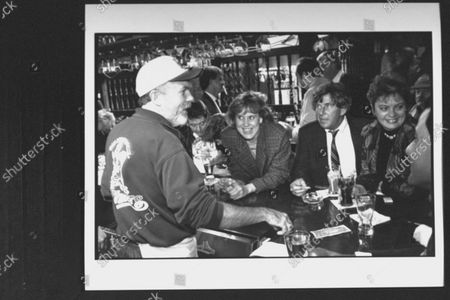 Stock Image of Bartender Eddie Doyle who inspired Cheers' Sam Malone, serving a group of customers at Bull & Finch Pub.