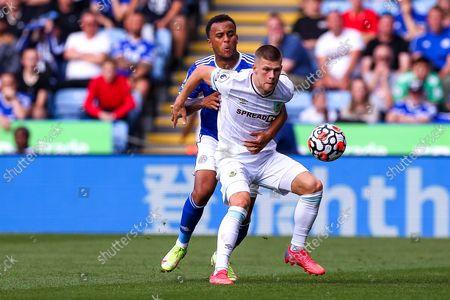 Johann Gudmundsson of Burnley holds off pressure from Ryan Bertrand of Leicester City