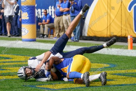 New Hampshire quarterback Bret Edwards (17) tumbles over Pittsburgh linebacker Phil Campbell III (24) after throwing the ball in the end zone during the first half of an NCAA college football game, in Pittsburgh. Edwards was flagged for intentional grounding on the play awarding Pittsburgh a safety