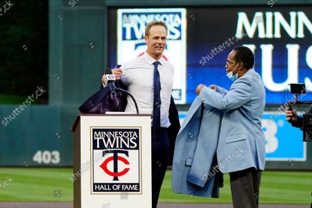 Former Minnesota Twins player Justin Morneau, left, sheds his jacket as former Twins great and Hall of Famer Rod Carew presents the new jacket after Morneau was inducted into the Twins' Hall of Fame prior to a baseball game against the Toronto Blue Jays, in Minneapolis