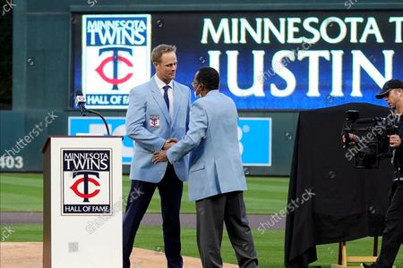 Former Minnesota Twins player Justin Morneau, left, shakes hands with former Twins great and Hall of Famer Rod Carew who presented him his new jacket after Morneau was inducted into the Twins' Hall of Fame prior to a baseball game against the Toronto Blue Jays, in Minneapolis