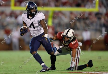 West Virginia running back Leddie Brown (4) escapes a tackle by Oklahoma linebacker Caleb Kelly (19) during the second half of an NCAA college football game in Norman, Okla