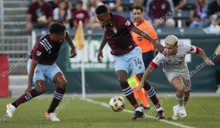 Colorado Rapids defender Auston Trusty, left, and midfielder Mark-Anthony Kaye (14) keep Toronto FC midfielder Yeferson Soteldo (30) away from the ball in the first half of an MLS soccer game in Denver