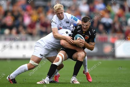 Josh Lewis of Dragons is tackled by Jac Morgan of Ospreys.