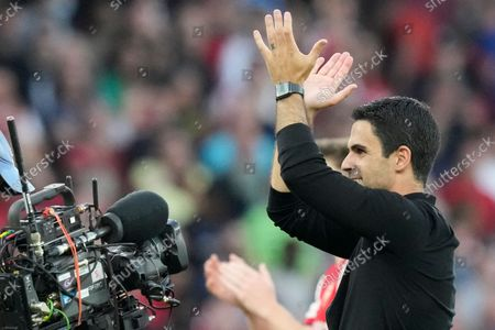 Stock Photo of Arsenal's manager Mikel Arteta greets supporters at the end of the English Premier League soccer match between Arsenal and Tottenham Hotspur at the Emirates stadium in London