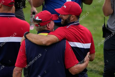 Team USA captain Steve Stricker hugs Team USA's Dustin Johnson after a Ryder Cup singles match at the Whistling Straits Golf Course, in Sheboygan, Wis