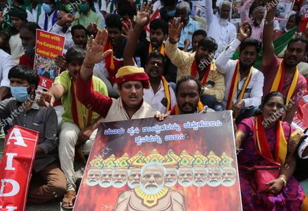 Farmers and members of various organisations shout slogans against the central government's new agriculture laws showing a painting that depicts India's Prime Minister Shri Narendra Modi, in support of 'Bharat Bandh' or the nationwide strike in Bangalore, India, 27 September 2021. Various political parties and activists protested and supported the Bharat Bandh, a nation-wide strike called by farmer unions against the farm bills.