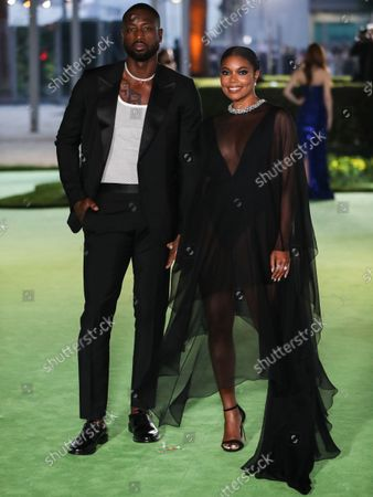 Former professional basketball player Dwyane Wade wearing a Gucci suit and Tiffany & Co. jewelry and wife/actress Gabrielle Union wearing an Alexandre Vauthier dress, Le Vian earrings, a Kallati bracelet, and Djula ring