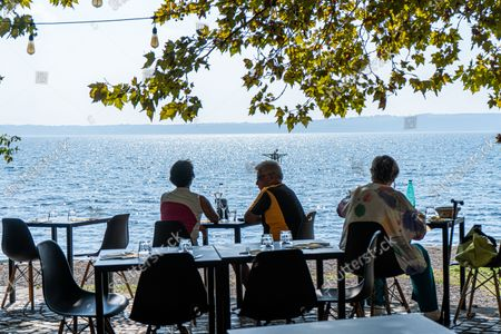 People dining alfresco overlooking lake Bracciano  on a hot and humid day as temperatures reach 31 Celsius