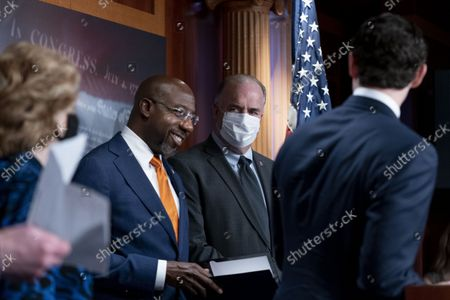 Sen. Jon Ossoff, D-Ga., right, accompanied by Sen. Debbie Stabenow, D-Mich., left, and Rep. Dan Kildee, D-Mich., second from right, introduces Sen. Raphael Warnock, D-Ga., second from left, to speak during a news conference on the inclusion of Solar Tax Credit Legislation in the reconciliation bill on Capitol Hill in Washington