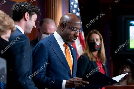 Stock Photo of Sen. Raphael Warnock, D-Ga., center, accompanied by, from left, Sen. Debbie Stabenow, D-Mich., Sen. Jon Ossoff, D-Ga., Rep. Dan Kildee, D-Mich., and Rep. Mikie Sherrill, D-N.J., right, takes the podium to speak during a news conference on the inclusion of Solar Tax Credit Legislation in the reconciliation bill on Capitol Hill in Washington