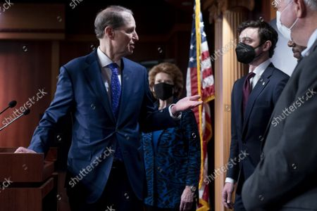 Sen. Ron Wyden, D-Ore., left, accompanied by Sen. Debbie Stabenow, D-Mich., center, and Rep. Dan Kildee, D-Mich., right, turns to Sen. Jon Ossoff, D-Ga., second from right, while speaking during a news conference on the inclusion of Solar Tax Credit Legislation in the reconciliation bill on Capitol Hill in Washington