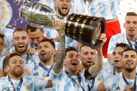 Argentina's Lionel Messi holds the trophy as he celebrates with the team after beating 1-0 Brazil in the Copa America final soccer match at the Maracana stadium in Rio de Janeiro, Brazil. European champion Italy will play Copa America winner Argentina next June. The inter-continental match is part of governing bodies UEFA and CONMEBOL building closer ties amid power struggles with FIFA over the future of soccer. UEFA confirmed plans Tuesday to stage the first of three planned editions of the inter-continental game in June at a venue to be confirmed. Naples has been suggested as a possible venue in the stadium now named for Argentina great Diego Maradona