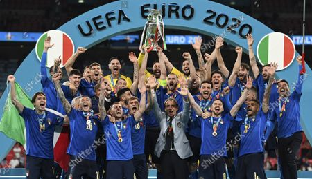 Italy's team celebrates with the trophy on the podium after winning the Euro 2020 soccer championship final between England and Italy at Wembley stadium in London. European champion Italy will play Copa America winner Argentina next June. The inter-continental match is part of governing bodies UEFA and CONMEBOL building closer ties amid power struggles with FIFA over the future of soccer. UEFA confirmed plans Tuesday to stage the first of three planned editions of the inter-continental game in June at a venue to be confirmed. Naples has been suggested as a possible venue in the stadium now named for Argentina great Diego Maradona