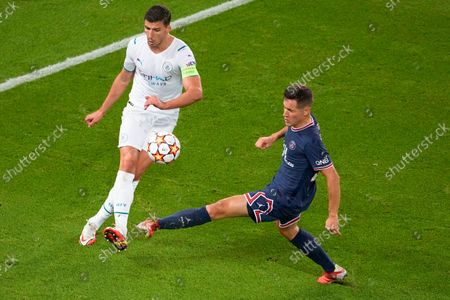 Manchester City's Ruben Dias, left, kicks the ball past PSG's Ander Herrera during the Champions League Group A soccer match between Paris Saint-Germain and Manchester City at the Parc des Princes in Paris