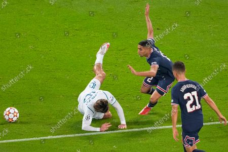 Manchester City's Jack Grealish, left, is fouled by PSG's Achraf Hakimi as PSG's Ander Herrera, right, watches during the Champions League Group A soccer match between Paris Saint-Germain and Manchester City at the Parc des Princes in Paris