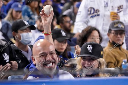 Actress Chelsea Handler, right, holds up a ball after a fan gave it to her as she sits with comedian Jo Koy during the fifth inning of a baseball game between the Los Angeles Dodgers and the San Diego Padres, in Los Angeles