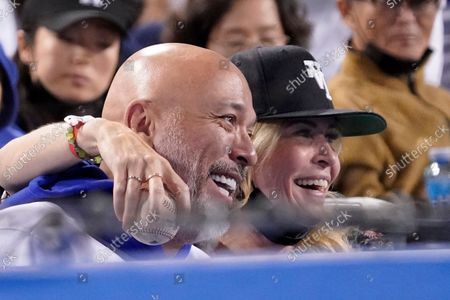 Stock Picture of Actress Chelsea Handler, right, hugs comedian Jo Koy after she received a ball from a fan during the fifth inning of a baseball game between the Los Angeles Dodgers and the San Diego Padres, in Los Angeles