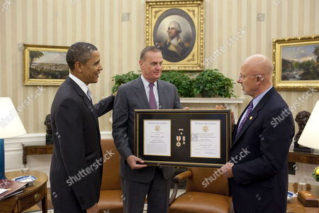 United States President Barack Obama and Director of National Intelligence James Clapper presenting the National Distinguished Service Medal to National Security Advisor General James L Jones in the Oval Office