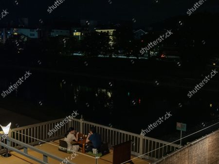 A couple enjoy a diner on a terrace in Pontocho, on September 25, in Kyoto, Japan. Recently the Mayor of Kyoto issued a declaration, declaring that if fiscal reforms are not carried out immediately, Kyoto City is likely to go bankrupt.
