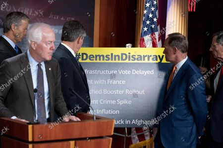 """Senate Minority Whip Sen. John Thune, R-S.D., left, Sen. Steve Daines, R-Mont., third from left, Sen. Pat Toomey, R-Pa., second from right, and Sen. John Barrasso, R-Wyo., right, turn to look at a sign that reads """"#DemsinDisarray"""" as Sen. John Cornyn, R-Texas, second from left, speaks at a news conference to call out the Democrats on numerous issues, on Capitol Hill in Washington"""