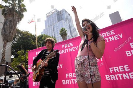 Britney Spears supporters Adrian Johnson, left, and Lucy Hall perform Spears' songs outside the Stanley Mosk Courthouse, in Los Angeles. A Los Angeles judge will hear arguments at a hearing Wednesday over removing Spears' father from the conservatorship that controls her life and money and whether the legal arrangement should be ended altogether