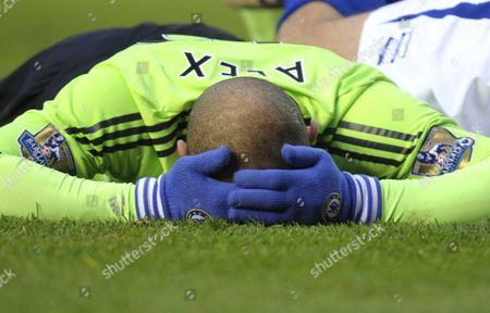 Alex Rodrigo Dias da Costa of Chelsea holds his head after colliding with Nikola Zigic