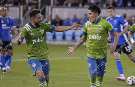 Seattle Sounders forward Raul Ruidiaz, right, celebrates with teammate Cristian Roldan, left, after scoring a goal on a penalty kick against the San Jose Earthquakes during the first half of an MLS soccer match, in San Jose, Calif
