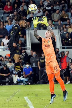 Portland Timbers goalkeeper Steve Clark, right, stops a shot next to forward Raheem Edwards during the second half of an MLS soccer match, in Los Angeles