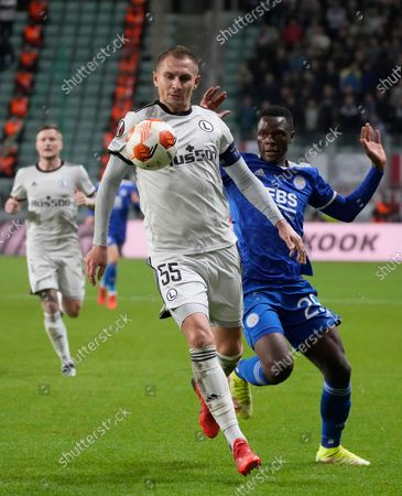 Legia's Artur Jedrzejczyk, centre, challenges for the ball with Leicester's Patson Daka during the Europa League Group C soccer match between Legia Warsaw and Leicester City in Warsaw, Poland