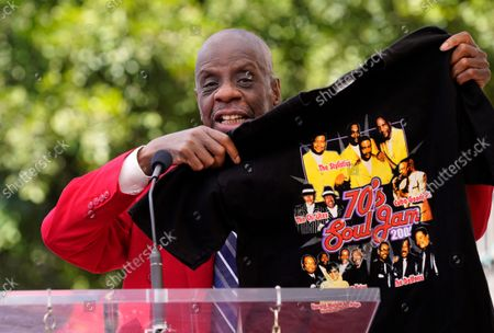 Stock Picture of Actor Jimmie Walker shows off a 2002 tour t-shirt featuring the R&B band The Chi-Lites during a ceremony to award them a star on the Hollywood Walk of Fame, in Los Angeles