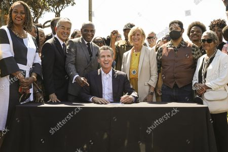 Los Angeles County Supervisor Holly Mitchell, in black and white dress, California Assemblyman Al Muratsuchi, California Senator Steven Bradford, Gov. Gavin Newsom, Los Angeles County Supervisor Janice Hahn and Anthony Bruce, great-great grandson of Charles and Willa Bruce, from left at table, during Newsom's signing of SB 796, authored by Ca. state Senator Bradford, authorizing the return of ocean-front land to the Bruce family, during a press conference held at Bruce's Beach in Manhattan Beach, CA, Thursday, Sept. 30, 2021. Some of the land making up Bruce's Beach was purchased by African American couple Willa and Charles Bruce, in 1912, establishing a resort that was open to African Americans. But by the 1920s, racial tensions grew in the beach community and the city condemned the properties. The park was renamed multiple times over the next 80 years and in 2007, was re-named for the Bruce family, responsible for trying to bring change and equality to the city. (Jay L. Clendenin / Los Angeles Times)