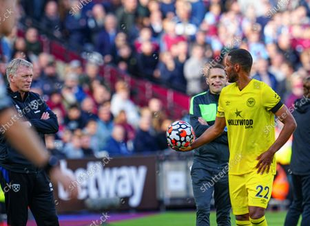 Mathias Zanka Jorgensen of Brentford clashes with West Ham manager David Moyes