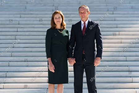 Associate Justice Amy Coney Barrett, left, stands with her husband, Jesse Barrett, at her investiture ceremony where she was welcomed by Chief Justice of the United States John Roberts, at the Supreme Court in Washington, . Barrett, appointed by President Donald Trump, took her place on the high court in October 2020, but the COVID-19 pandemic delayed the ceremony