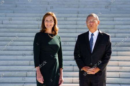 Associate Justice Amy Coney Barrett, left, is escorted for a traditional investiture ceremony by Chief Justice of the United States John Roberts, at the Supreme Court in Washington, . Barrett, appointed by President Donald Trump, took her place on the high court in October 2020, but the COVID-19 pandemic delayed the ceremony