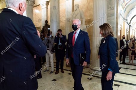 President Joe Biden walks to greet Rep. Steny Hoyer, D-Md., left, next to House Speaker Nancy Pelosi of Calif., as Biden arrives for a meeting with House Democrats, on Capitol Hill in Washington