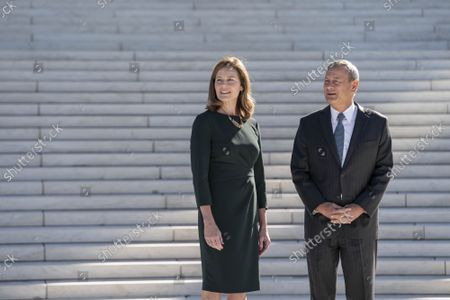 Supreme Court Justice Amy Coney Barrett and  Chief Justice of the Supreme Court John Roberts participate in a photo-op outside of the Supreme Court of the United States following a investiture ceremony in Washington, DC on Friday October 1, 2021.
