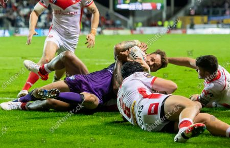 Leeds's Richie Myler scores a try against St Helens as Regan Grace & Lachlan Coote desperately try to hold him up.