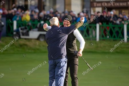 Danny Willett of England celebrates with his amateur partner, American investment banker and philanthropist Jimmy Dunne, on the 18th green of the Old Course, St Andrews, after winning the Alfred Dunhill Links Championship; The Old Course, St Andrews Links, Fife, Scotland; European Tour, Alfred Dunhill Links Championship, Fourth round.