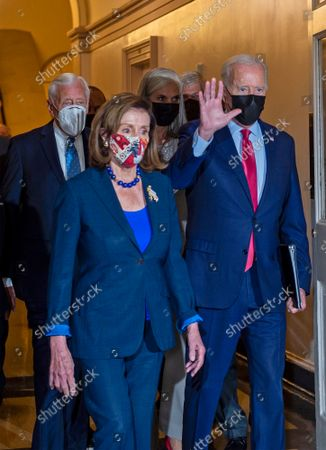 United States President Joe Biden, right, escorted by Speaker of the US House of Representatives Nancy Pelosi (Democrat of California), front left, and US House Majority Leader Steny Hoyer (Democrat of Maryland), back left, waves to the media as he arrives for talks on the infrastructure bill at the US Capitol in Washington, DC,.