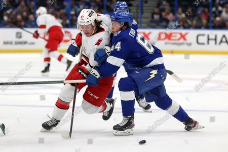 Carolina Hurricanes' Jamieson Rees fights through the check of Tampa Bay Lightning's Jack Thompson during the first period of a preseason NHL hockey game, in Tampa, Fla