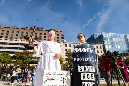 Sisters Lauren Biggs (left) and Katherine Johnson attend the Women's March Rally for Abortion Justice in Washington, DC dressed as wounded and bleeding Lady Justice and Ruth Bader Ginsburg.  Protesters demand the US government protect women's reproductive rights and access to abortion nationwide.  Specifically, they are calling on Congress to pass the Women's Health Protection Act (WHPA) and EACH Act, which guarantee abortion access and require it to be covered by insurance.  More than 600 satellite protests are happening nationwide on October 2.  The events are partly in response to restrictive anti-abortion laws recently passed in Texas and Mississippi, and the Supreme Court's refusal to strike down the Texas law.