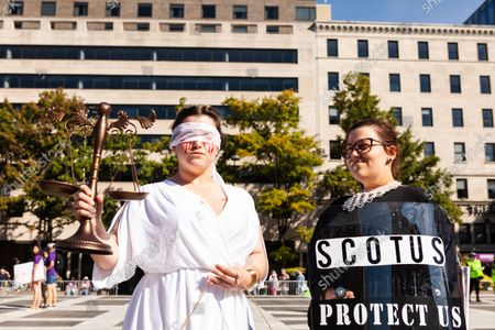Stock Picture of Sisters Lauren Biggs (left) and Katherine Johnson attend the Women's March Rally for Abortion Justice in Washington, DC dressed as wounded and bleeding Lady Justice and Ruth Bader Ginsburg.  Protesters demand the US government protect women's reproductive rights and access to abortion nationwide.  Specifically, they are calling on Congress to pass the Women's Health Protection Act (WHPA) and EACH Act, which guarantee abortion access and require it to be covered by insurance.  More than 600 satellite protests are happening nationwide on October 2.  The events are partly in response to restrictive anti-abortion laws recently passed in Texas and Mississippi, and the Supreme Court's refusal to strike down the Texas law.
