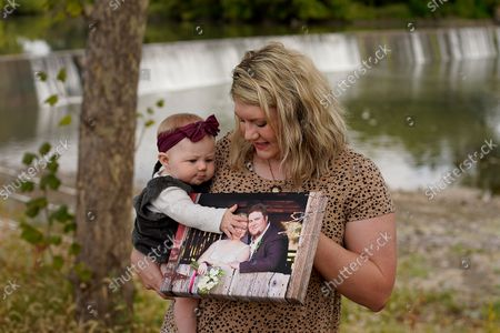 Aubrea Baker displays her wedding photo as she and her 7-month-old daughter Haylen visit one of her late husband's favorite fishing spots, in Burlington, Kan. Her husband, Danny Baker, was among the 700,000 U.S. victims of COVID-19, dying on Sept. 14 after testing positive in July