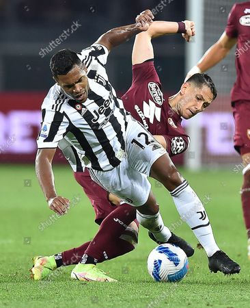 Torino's Sasa Lukic and Juventus' Alex Sandro (front) in action during the Italian Serie A soccer match Torino FC vs Juventus FC at Olimpico Grande Torino Stadium in Turin, Italy, 02 October 2021.