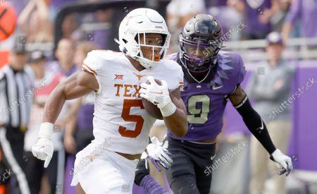 Texas running back Bijan Robinson (5) runs for a touchdown as TCU cornerback C.J. Ceasar II (9) pursues during the first half of an NCAA college football game, in Fort Worth, Texas