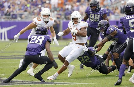 Stock Picture of Texas running back Bijan Robinson (5) carries the the ball as a host of TCU defenders close in during the first half of an NCAA college football game, in Fort Worth, Texas