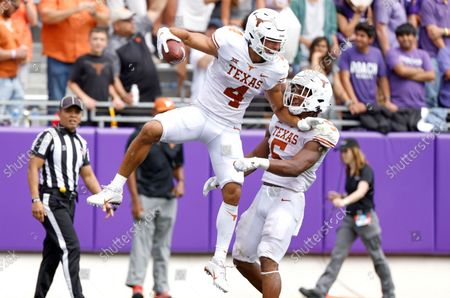 Texas wide receiver Jordan Whittington (4) and teammate running back Bijan Robinson (5) celebrate Whittington's touchdown pass against TCU during the second half of an NCAA college football game, in Fort Worth, Texas. Texas won 32-27