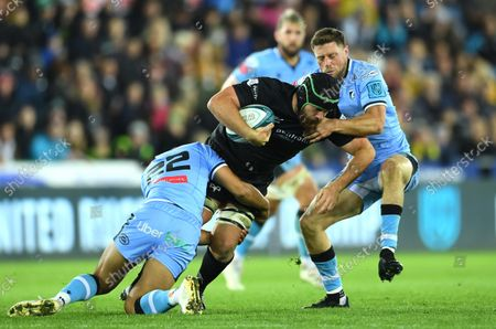 Morgan Morris of Ospreys is tackled by Ben Thomas and Rhys Priestland of Cardiff.